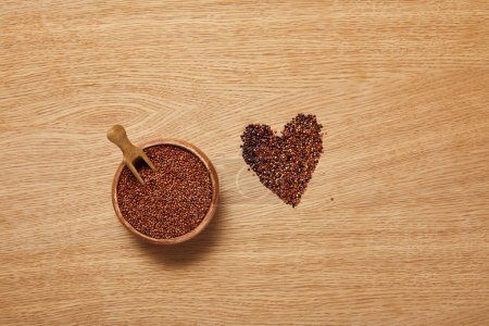 Photo for Top view of red quinoa seeds in wooden bowl with spatula near heart sign - Royalty Free Image