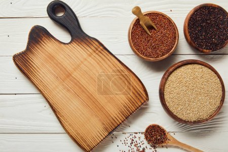 Photo for Top view of white, black and red quinoa in wooden bowls near chopping board on white table - Royalty Free Image