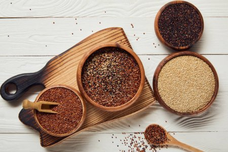 Photo for Top view of white, black and red quinoa in wooden bowls on white table with chopping board - Royalty Free Image