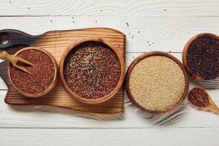 Foto de Vista superior de semillas de quinua blanca, negra y roja en cuencos de madera sobre mesa blanca con tabla de cortar - Imagen libre de derechos