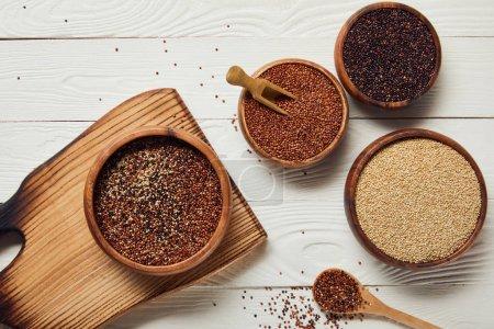 Photo pour Vue supérieure des graines brutes de quinoa blanc, noir et rouge dans des cuvettes en bois sur la table blanche avec la planche à découper - image libre de droit