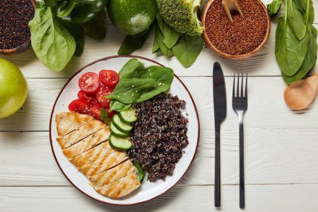Photo for Top view of served delicious quinoa with grilled chicken breast and vegetables on white plate on wooden table - Royalty Free Image