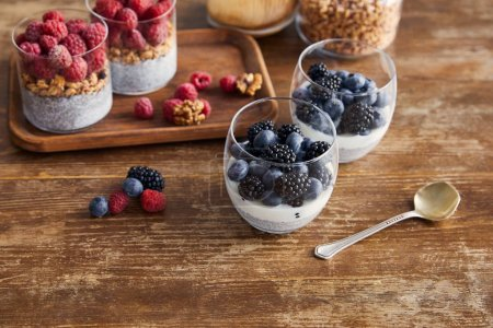 Photo for Breakfast with oat flakes, yogurt with chia seeds and berries on wooden tray on table - Royalty Free Image