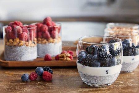 Foto de Enfoque selectivo de yogur con semillas de chía, frambuesas, arándanos y moras en vasos en la cocina - Imagen libre de derechos