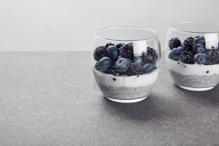 Photo for Delicious yogurt with chia seeds and berries in glasses isolated on grey - Royalty Free Image