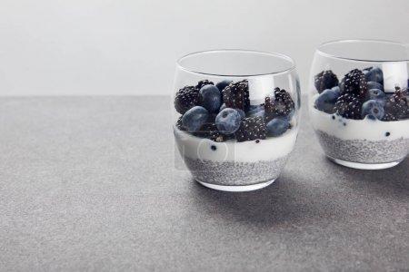 Photo pour Délicieux yaourt aux graines de chia et baies dans des verres isolés sur gris - image libre de droit