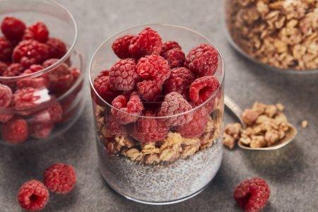 Foto de Enfoque selectivo de yogur sabroso con frambuesas, copos de avena y semillas de chía cerca de la cucharadita en la superficie de mármol - Imagen libre de derechos