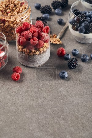 Photo for Yogurt with chia seeds, oat flakes and raspberries near teaspoon and glass with blueberries, blackberries and yogurt on marble surface - Royalty Free Image