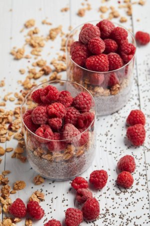 Photo for Selective focus of raspberries, oat flakes and yogurt with chia seeds in glasses near scattered oat, berries and seeds on white wooden table - Royalty Free Image