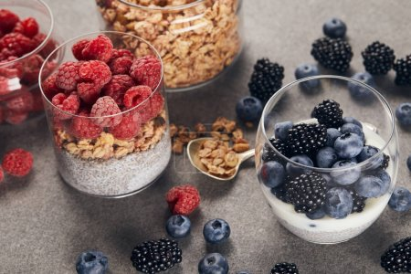 Photo for Selective focus of tasty yogurt with chia seeds, berries and oat flakes in glasses near teaspoon on marble surface - Royalty Free Image