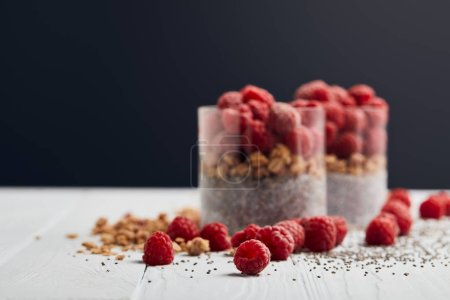 Photo for Selective focus of scattered raspberries, chia seeds and oat flakes near glasses with yogurt and berries on white wooden table isolated on black - Royalty Free Image