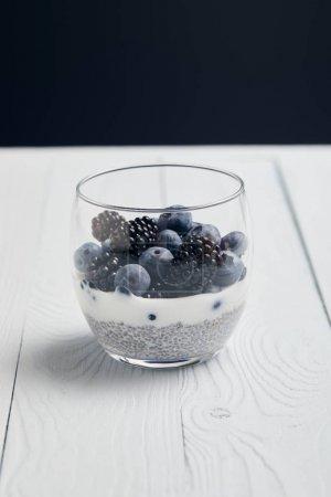 Photo pour Verre avec des myrtilles, des mûres et du yaourt avec des graines de sur la table en bois blanche d'isolement sur le noir - image libre de droit