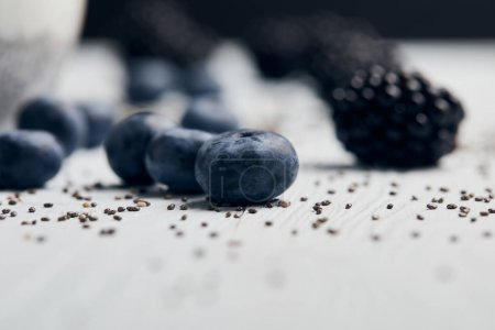 Photo for Close up view of blueberries, blackberries and scattered chia seeds on white wooden table - Royalty Free Image