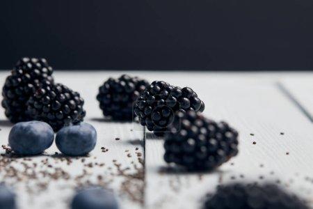 Photo pour L'accent sélectif des mûres, des bleuets et des graines de dispersées sur la table isolée sur le noir - image libre de droit