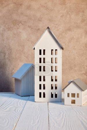 Foto de Casas modelos en mesa de madera blanca cerca de la pared texturizada, concepto de bienes raíces - Imagen libre de derechos