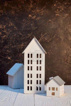 Photo pour Maisons modèles sur table en bois blanc près du mur texturé brun, concept immobilier - image libre de droit
