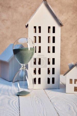 Photo pour Maisons modèles et sablier sur table en bois blanc près du mur texturé, concept immobilier - image libre de droit