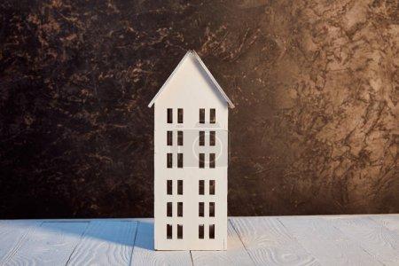 Photo pour Modèle de maison sur la table en bois près du mur texturé brun, concept d'immobiliers - image libre de droit