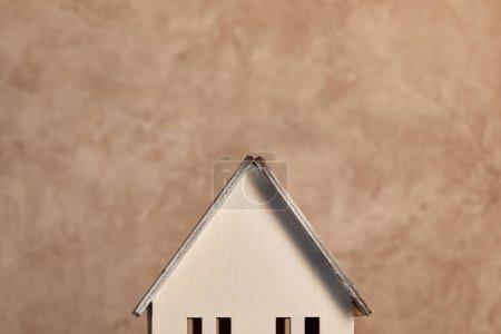 Photo pour Toit du modèle de maison près du mur texturé beige, concept d'immobiliers - image libre de droit