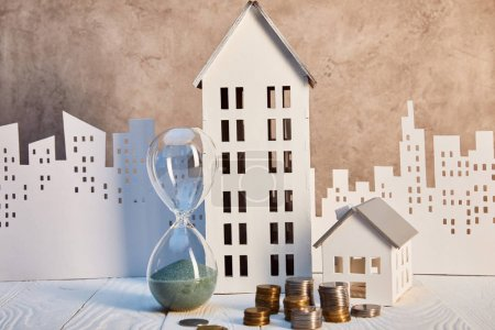Photo for Houses models and hourglass on white wooden table with coins, real estate concept - Royalty Free Image