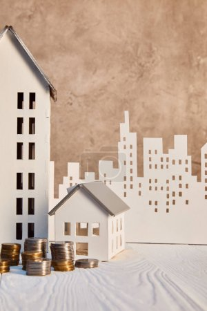 Foto de Monedas y casas modelos en mesa de madera blanca cerca de la pared con textura marrón y la ciudad del papel, concepto de bienes raíces - Imagen libre de derechos