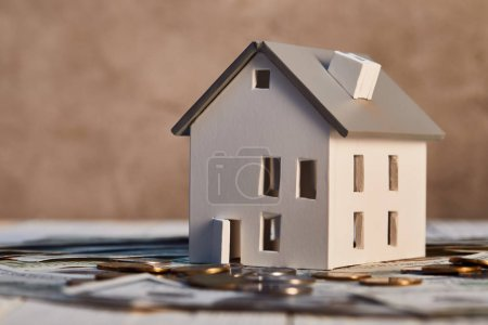 house model on dollar banknotes and coins, real estate concept