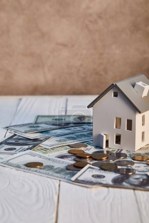 Photo for House model on dollar banknotes and coins on wooden table, real estate concept - Royalty Free Image