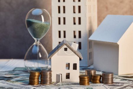 houses models and hourglass on cash and coins, real estate concept