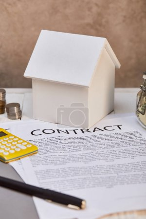 house model, coins, calculator near contract and moneybox, real estate concept