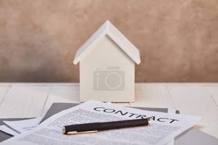 white house model on white wooden table with contract near brown textured wall, real estate concept