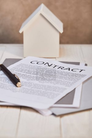 Photo for White house model on white wooden table with contract and pen near brown textured wall, real estate concept - Royalty Free Image