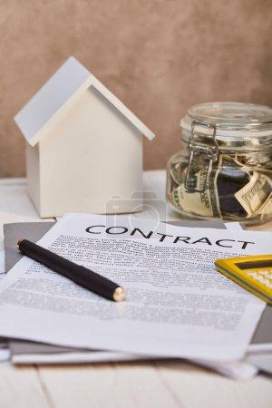 Photo pour Modèle de maison blanche sur la table en bois blanche avec le contrat et la boîte d'argent près du mur texturé brun, concept d'immobiliers - image libre de droit