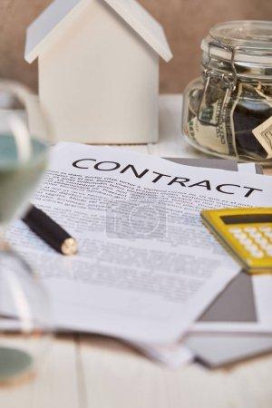 Photo pour Focus sélectif du modèle de maison, contrat et moneybox, concept d'immobiliers - image libre de droit