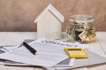 Photo pour Modèle de maison sur la table en bois blanche avec le contrat, la calculatrice et l'argent près du mur texturé brun, concept d'immobiliers - image libre de droit