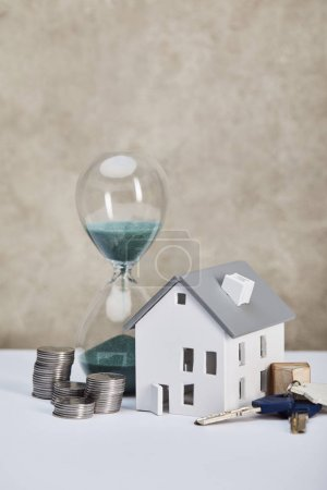 Photo for House model on white table with hourglass, silver coins and keys, real estate concept - Royalty Free Image