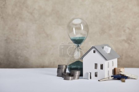 Photo for House model on white table with hourglass, coins and keys, real estate concept - Royalty Free Image