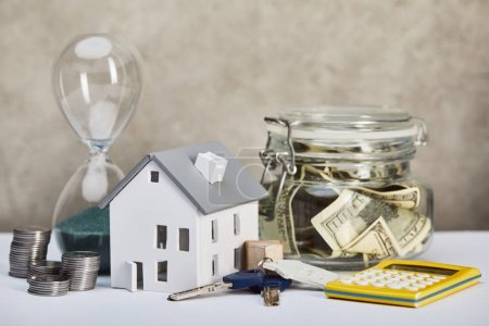 Photo for House model on white table with hourglass, calculator, money and keys, real estate concept - Royalty Free Image
