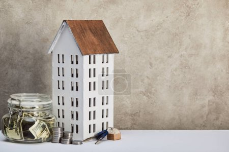 Photo for House model, moneybox with dollar banknotes, keys and silver coins on white table on grey background, real estate concept - Royalty Free Image