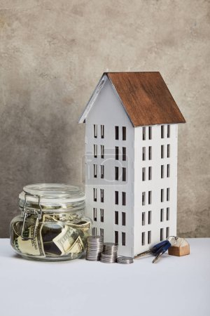 house model, moneybox with dollar banknotes, keys and silver coins on white table, real estate concept