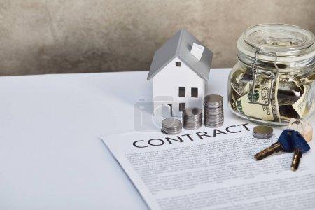 Photo pour Modèle de maison sur table blanche avec des pièces d'argent, clés, contrat et tirelire, concept immobilier - image libre de droit