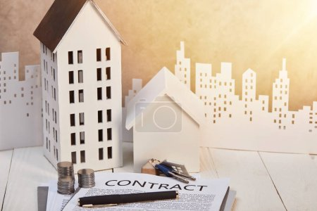 houses models on white wooden table with contract, coins and keys near white paper cut city, real estate concept
