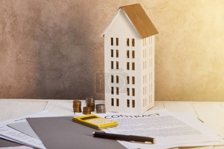 Photo for House model near coins, calculator, pen and contract on table with sunlight, real estate concept - Royalty Free Image