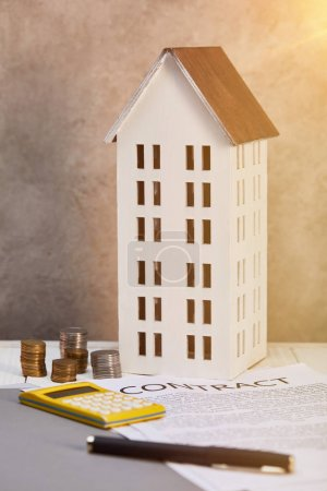 house model near coins, calculator and contract on table with sunlight, real estate concept