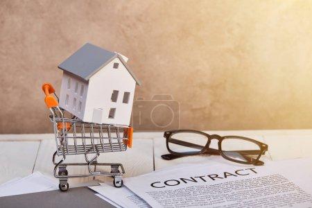 Photo for House model in small shopping cart on white wooden table with contract and glasses in sunlight, real estate concept - Royalty Free Image