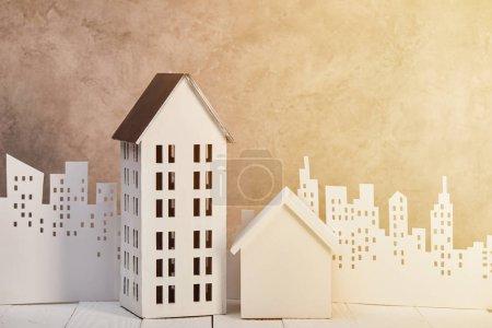 Photo pour Maisons modèles sur la table en bois blanc près de papier blanc coupé ville en plein soleil, concept immobilier - image libre de droit