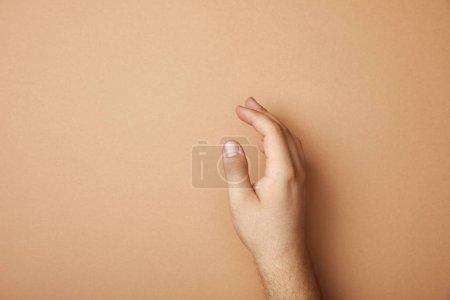 Ausgeschnittene Ansicht der männlichen Hand auf beigem Hintergrund mit Kopierraum
