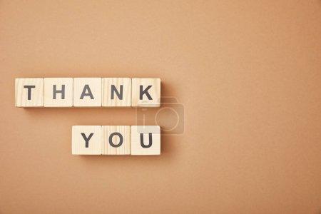 Photo pour Vue supérieure des cubes en bois avec le lettrage de remerciement sur le fond beige avec l'espace de copie - image libre de droit