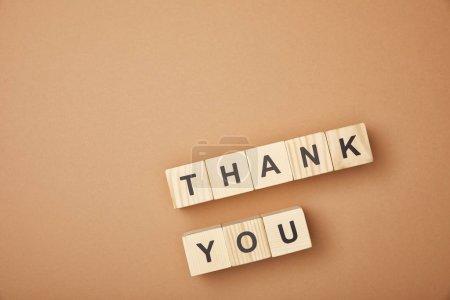 Photo pour Vue supérieure des cubes en bois avec des mots de remerciement sur le fond beige - image libre de droit