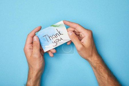 Photo pour Vue recadrée de l'homme retenant la carte de voeux avec le lettrage de remerciement sur le fond bleu - image libre de droit