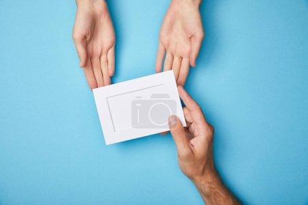 Photo pour Vue recadrée de l'homme donnant carte blanche vide dans le cadre à la femme sur fond bleu - image libre de droit